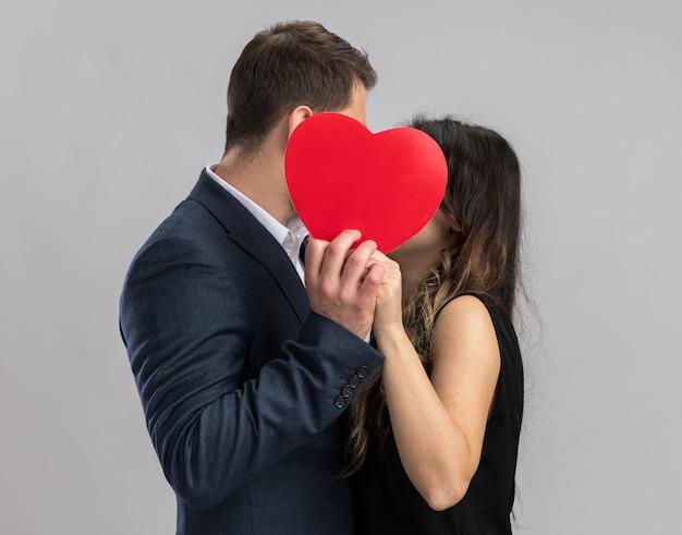 Jovem casal lindo homem e mulher se beijando atrás de um coração vermelho, felizes e apaixonados, comemorando o dia dos namorados