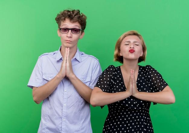 Jovem casal lindo homem e mulher segurando as palmas das mãos juntas como se estivesse orando com expressão de esperança em pé sobre a parede verde
