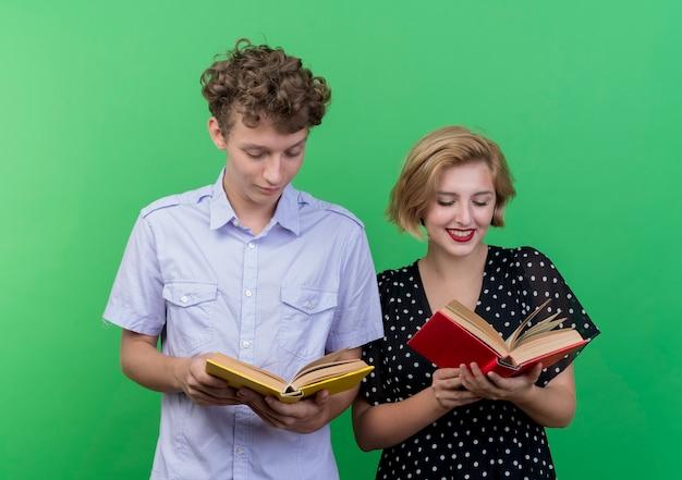 Jovem casal lindo homem e mulher segurando livros, olhando para eles com um sorriso no rosto em pé sobre a parede verde