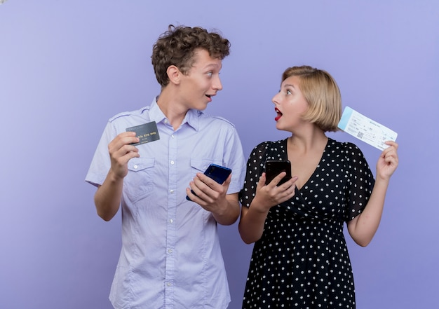 Jovem casal lindo homem e mulher segurando smartphones e cartão de crédito com passagens aéreas felizes e surpresos olhando um para o outro sobre a parede azul