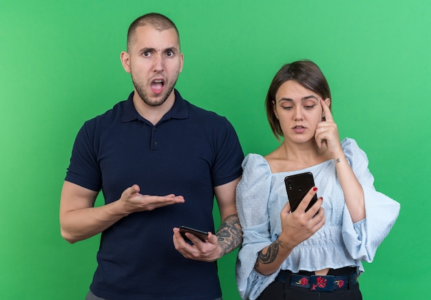 Jovem casal lindo homem e mulher segurando smartphones parecendo confuso e descontente em pé