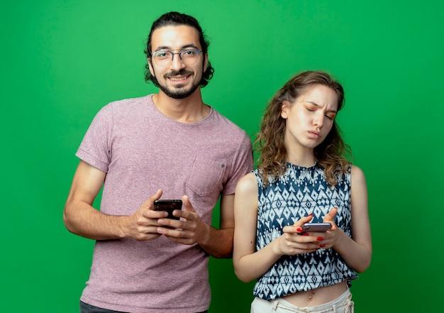Jovem casal lindo homem e mulher sorrindo segurando um smartphone ao lado de sua namorada descontente com o celular sobre a parede verde