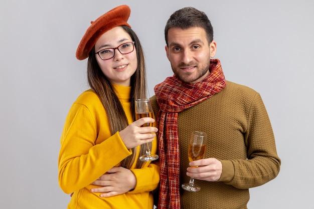 Jovem casal lindo homem feliz e mulher sorridente na boina com copos de champanhe sorrindo alegremente feliz no amor juntos comemorando o dia dos namorados em pé sobre um fundo branco