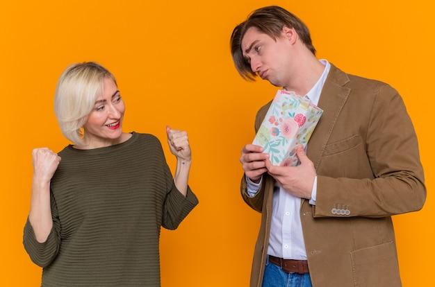 Jovem casal lindo homem triste dando um presente para sua adorável namorada surpresa, felizes e apaixonados, celebrando o dia internacional da mulher em pé sobre a parede laranja