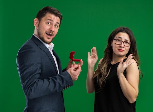 Jovem casal lindo lindo homem segurando uma caixa vermelha com um anel de noivado vai fazer uma proposta para sua linda namorada enquanto ela faz um gesto de pare com as mãos em pé sobre a parede verde