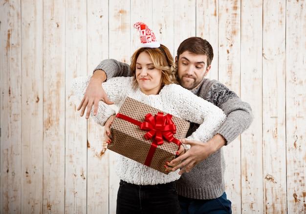 Jovem casal lindo lutando pelo presente de natal ao longo da parede de madeira