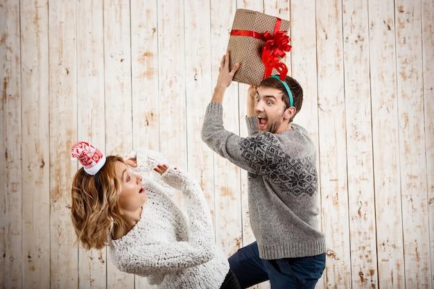 Jovem casal lindo lutando pelo presente de natal sobre a superfície de madeira