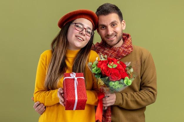 Jovem casal lindo mulher feliz em boina com presente e homem com buquê de rosas vermelhas, olhando para a câmera, sorrindo, feliz e apaixonado juntos, comemorando o dia dos namorados em pé sobre a parede verde
