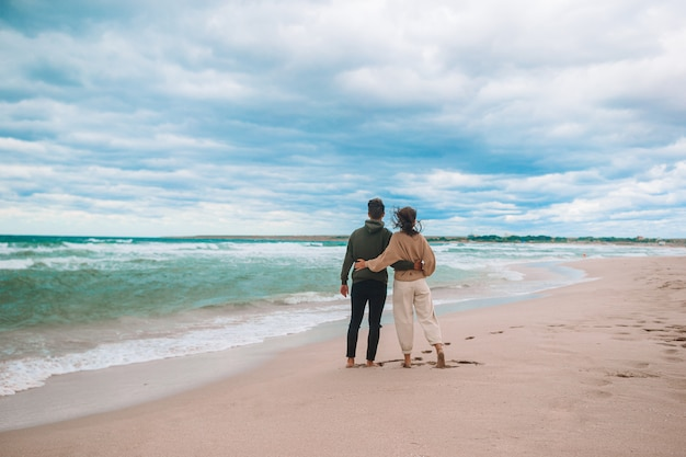 Jovem casal lindo na praia em tempo ventoso e nublado