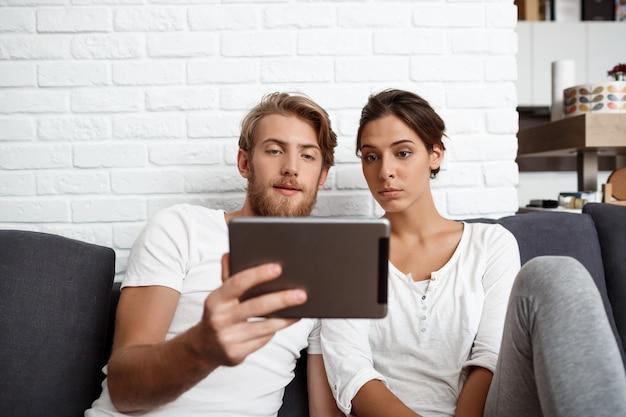 Jovem casal lindo olhando tablet sentado no sofá em casa.