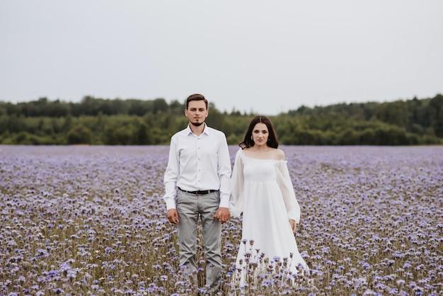 Jovem casal lindo parado em um campo de flores roxas