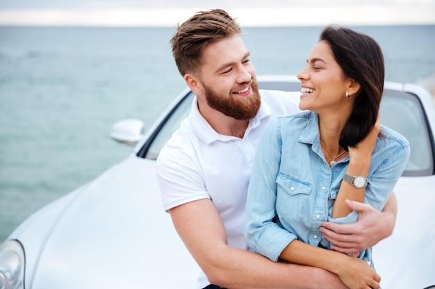 Jovem casal lindo se abraçando em pé perto do carro à beira-mar