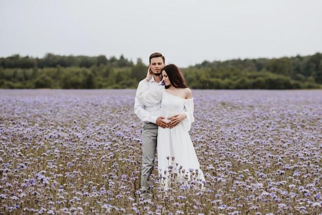 Jovem casal lindo se abraçando em um campo roxo florescendo