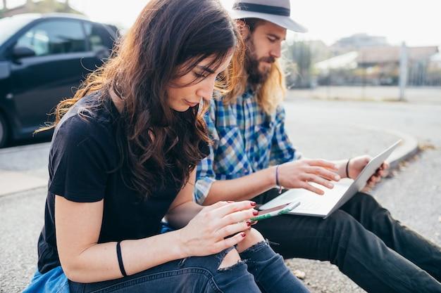 Jovem casal lindo sentado ao ar livre, usando o computador e smartphone