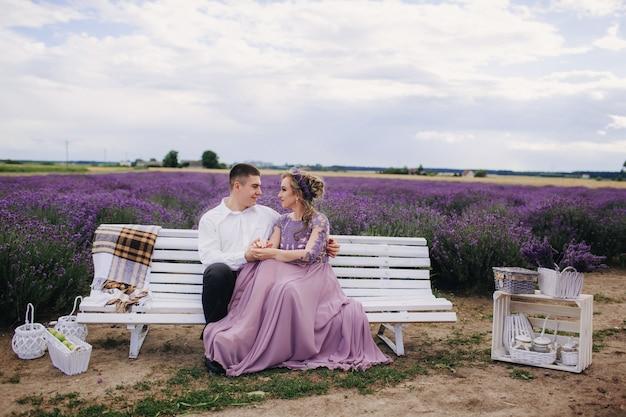 Jovem casal lindo sentado em um banco branco em um campo de lavanda