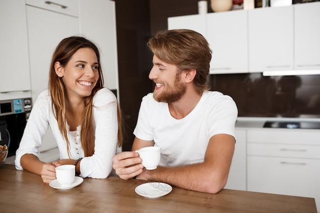 Jovem casal lindo sentado na cozinha, bebendo café da manhã sorrindo.