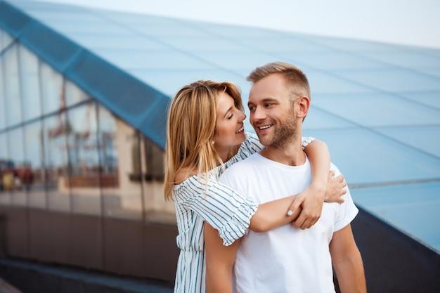 Jovem casal lindo sorrindo, abraçando, andando pela cidade.