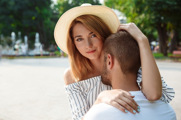 Jovem casal lindo sorrindo, abraçando, caminhando no parque.