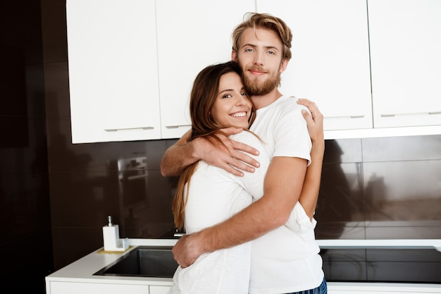 Jovem casal lindo sorrindo abraçando em pé na cozinha.