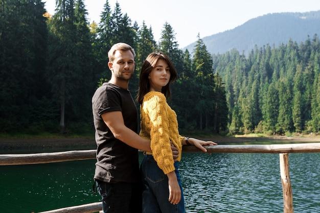 Jovem casal lindo sorrindo, abraçando, lago e montanhas
