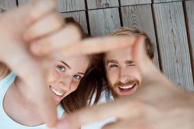 Jovem casal lindo sorrindo, deitado sobre tábuas de madeira, fazendo o quadro com as mãos foco nos rostos