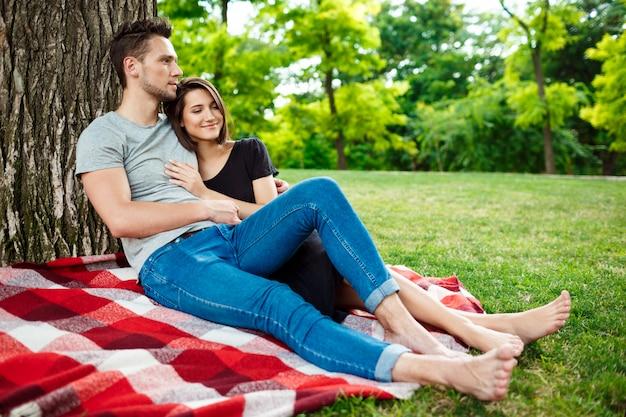 Jovem casal lindo sorrindo, descansando no piquenique no parque.