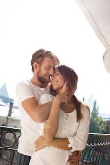 Jovem casal lindo sorrindo desfrutando de pé na varanda.