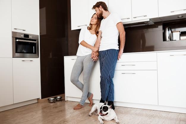 Jovem casal lindo sorrindo em pé na cozinha com cão pug.