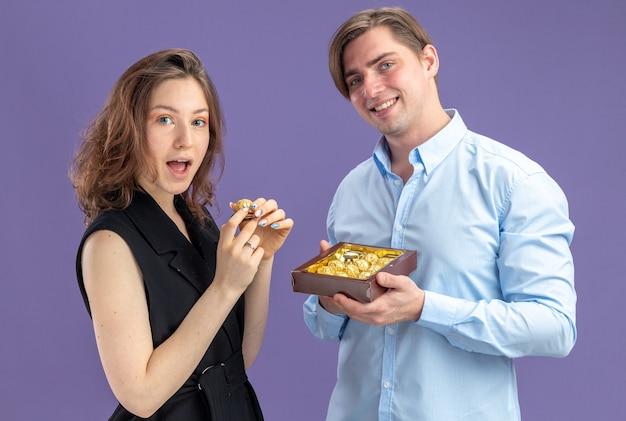 Jovem casal lindo sorrindo homem oferecendo bombons de chocolate para sua adorável namorada comemorando o dia dos namorados em pé sobre uma parede azul