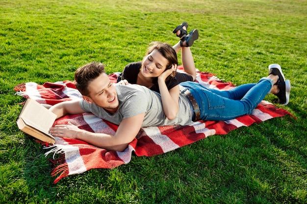 Jovem casal lindo sorrindo lendo no parque.