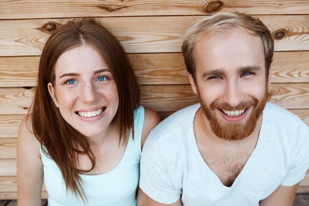 Jovem casal lindo sorrindo, posando sobre fundo de tábuas de madeira
