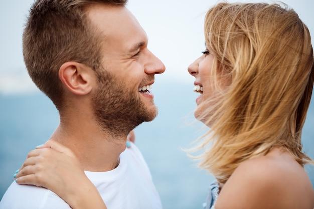 Jovem casal lindo sorrindo, regozijando-se, vista para o mar.