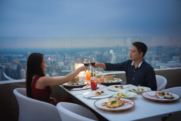 Jovem casal lindo tendo um jantar romântico no telhado à noite.