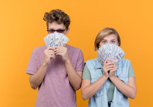 Jovem casal lindo vestindo roupas casuais, homem e mulher, mostrando dinheiro e parecendo surpreso com a laranja