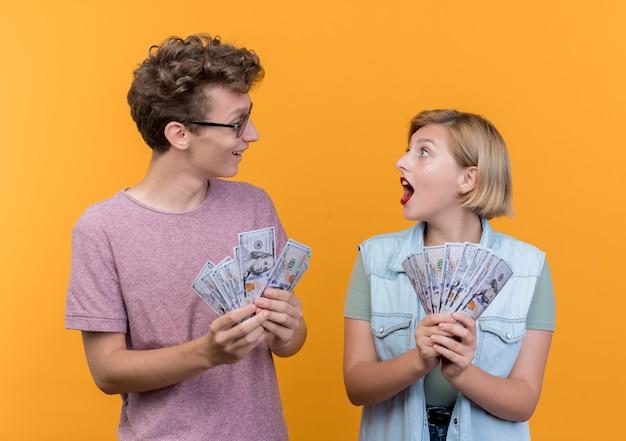 Jovem casal lindo vestindo roupas casuais, homem e mulher, mostrando dinheiro e parecendo surpreso em pé sobre a parede laranja