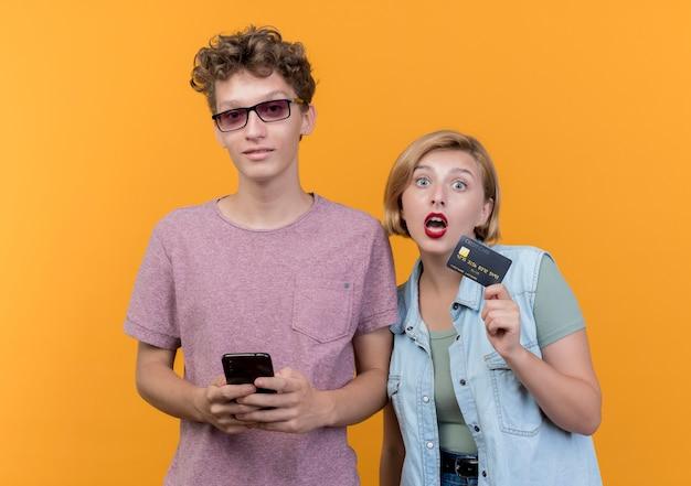 Jovem casal lindo vestindo roupas casuais, homem segurando um smartphone, parecendo confiante em pé perto de sua namorada surpresa com cartão de crédito na parede laranja