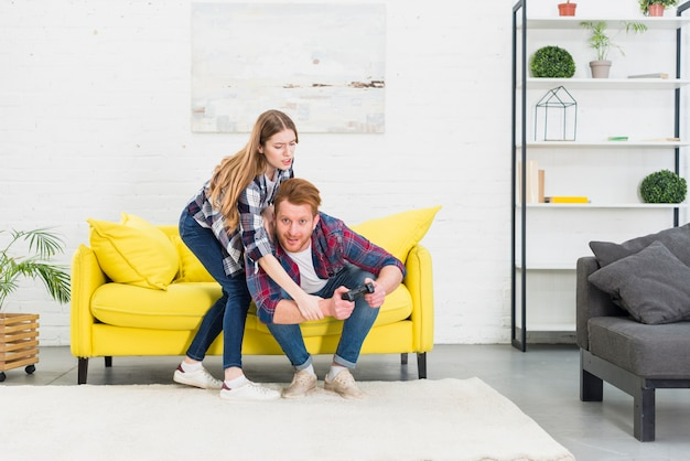 Jovem casal lutando por joystick enquanto jogava videogame em casa