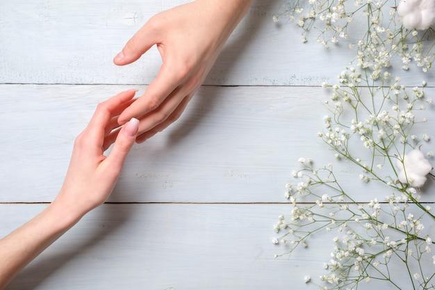 Jovem casal mão na mesa de madeira azul com flores