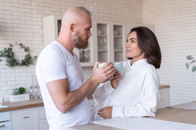 Jovem casal, marido e mulher em casa na cozinha, sorriso feliz, risada, tomam café pela manhã