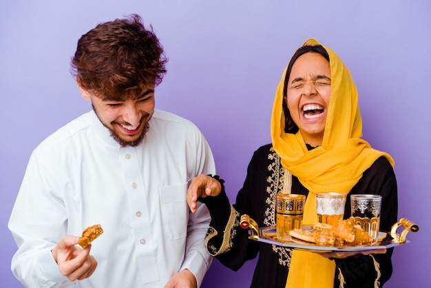 Jovem casal marroquino bebendo chá comemorando o mês do ramadã isolado em fundo roxo