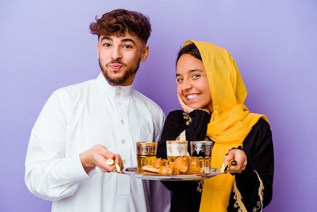 Jovem casal marroquino bebendo chá comemorando o mês do ramadã isolado em roxo Foto Premium