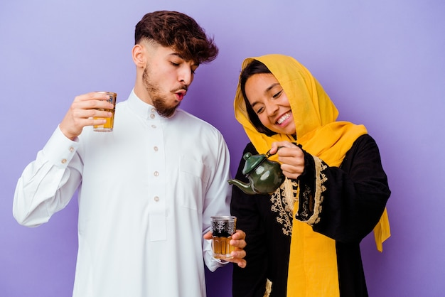 Jovem casal marroquino bebendo chá comemorando o mês do ramadã isolado em roxo