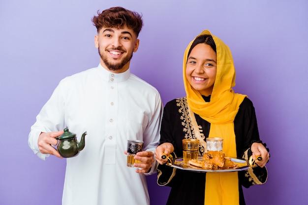 Jovem casal marroquino bebendo chá comemorando o mês do ramadã isolado na parede roxa