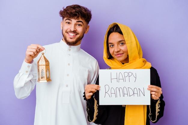 Jovem casal marroquino vestindo um traje árabe típico, comemorando o ramadã isolado em um fundo roxo.