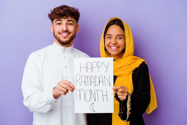 Jovem casal marroquino vestindo um traje árabe típico, comemorando o ramadã isolado no roxo