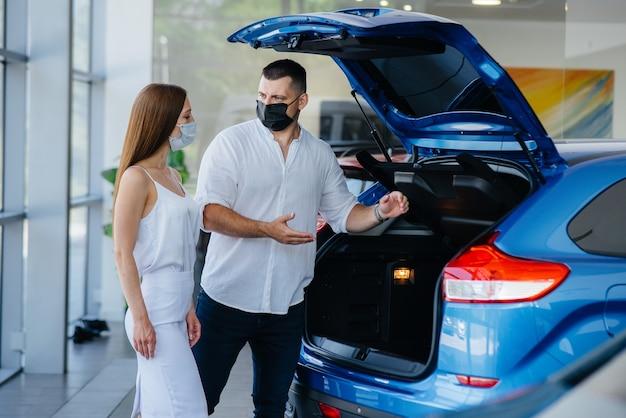 Jovem casal mascarado escolhe um novo veículo e consulta um representante da concessionária no período da pandemia. venda de carros e vida durante a pandemia.