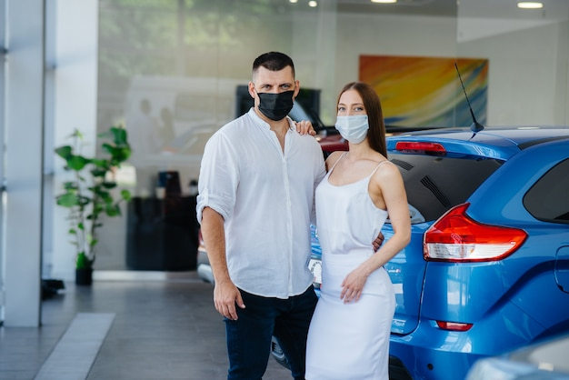 Jovem casal mascarado escolhe um novo veículo e consulta um representante da concessionária no período da pandemia.