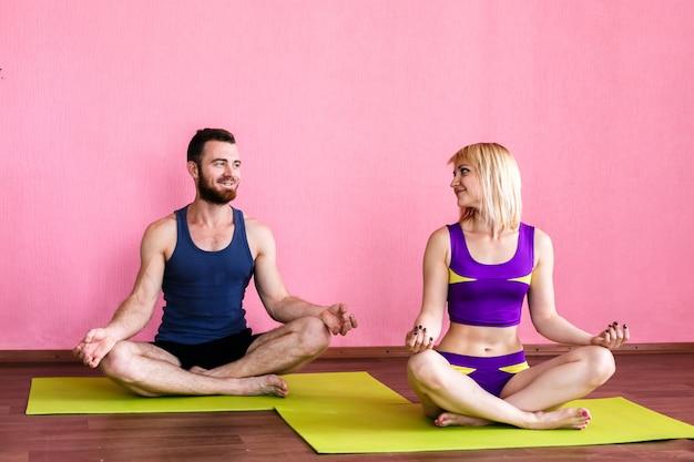 Jovem casal meditando na posição de lótus.
