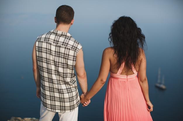 Jovem casal menino e menina de mãos dadas em um penhasco com vista para o mar