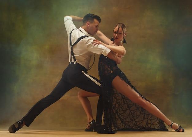 Jovem casal moderno e flexível dançando tango no estúdio retrato da moda de uma dança atraente